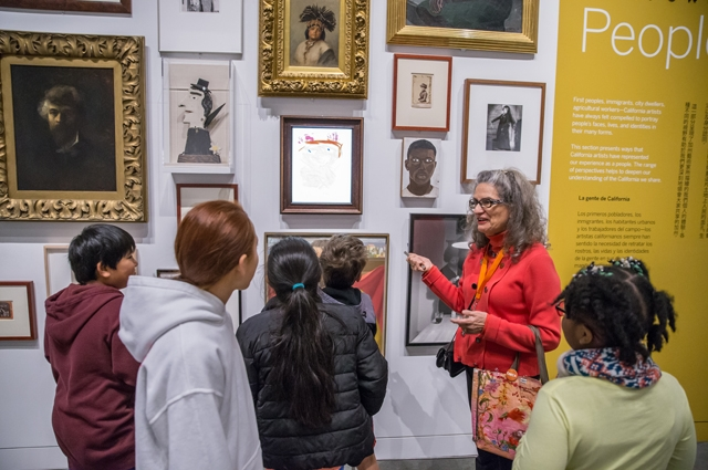A Docent points at a group of paintings while a group of students listen