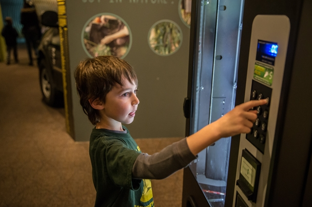 A young child putting money in a vending machine that sells Citizen Science kits at the Oakland Museum of California gallery of Natural Sciences