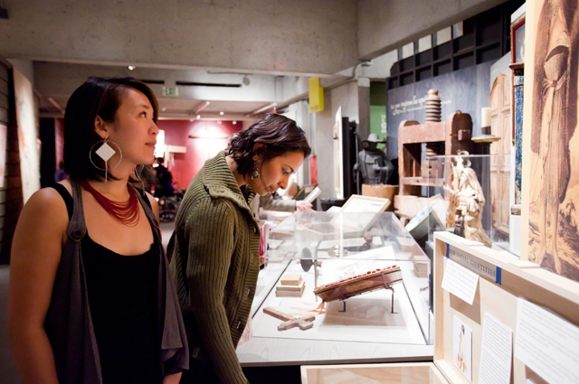 Two women view sculptures in glass cases