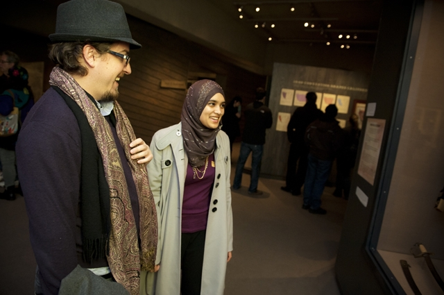 A man and woman smile and laugh at artwork in a case