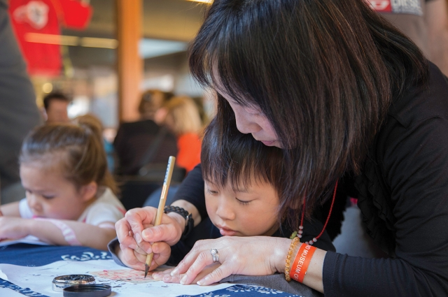 A mother and son do Lunar New Year crafts at OMCA