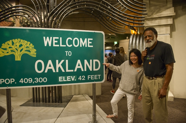 A man and woman point at a sign that reads Welcome to Oakland