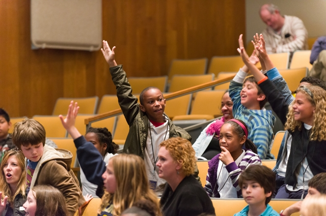 A young boy in an auditorium full of students stands up to raise his hand