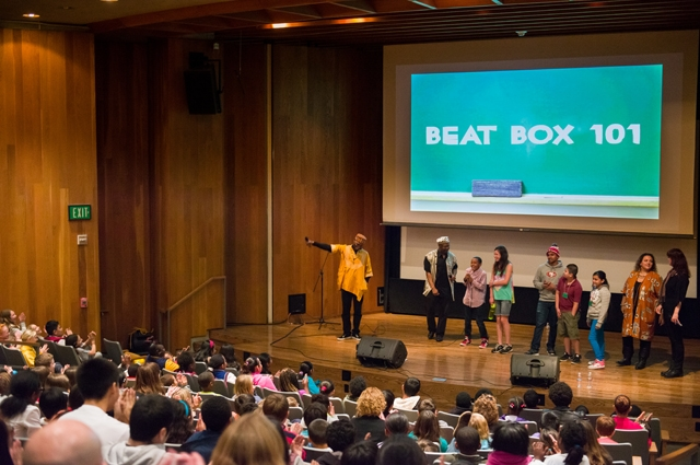 """Beat Box 101"" displayed on the large screen in the Moore Theater with a large class filling the seats"