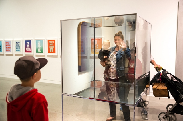 A mother waves to her child from behind a large glass box