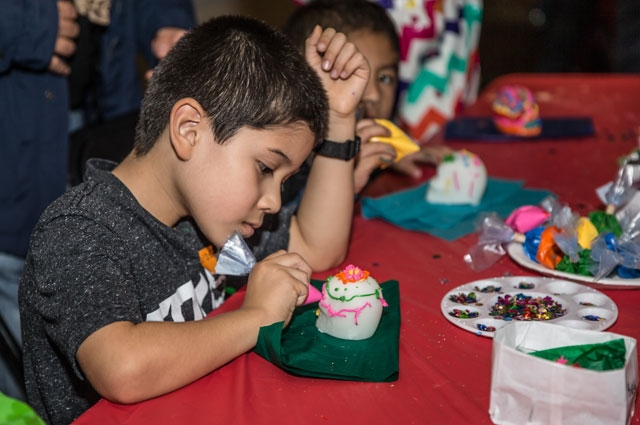 Child decorating sugar skulls at the Oakland Museum of California's Days of the Dead Community Celebration