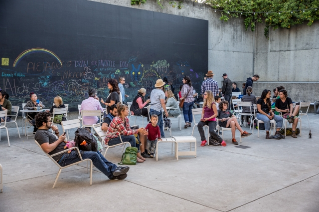 A large group of people hang out in OMCA's Oak Street Plaza