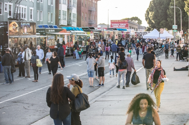 10th Street filled with food trucks and large crowds walking and ordering food