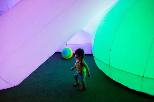 A young child playing inside colorful inflatable sculpture by FriendsWithYou at Oakland Museum of California