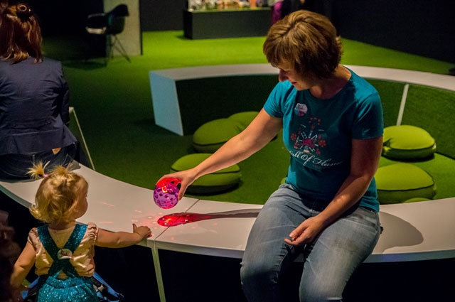 Adult and child playing with LED ball inside Nature's Gift: Humans, Friends and the Unknown at Oakland Museum of California
