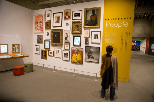 A woman views a large arrangement of paintings in the art gallery