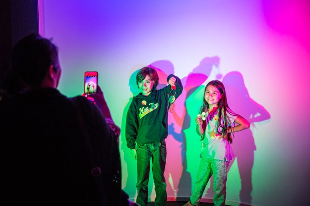 Children pose for a photo inside colorful exhibition Nature's Gift: Humans, Friends and the Unknown at Oakland Museum of California