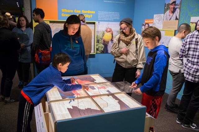A group of people view a map on a table top stand