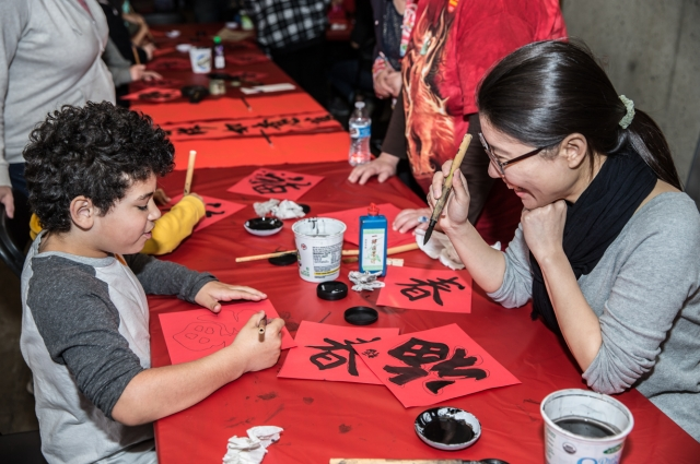 A child and adult do Lunar New Year crafts at OMCA