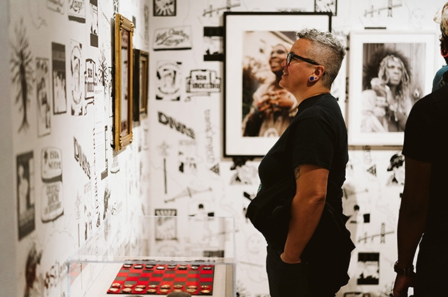 A side view of a person with glasses and short hair in Queer California looking at a wall hanging and smiling