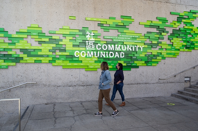 Two staff members walk past the green tiled wall reading Community.