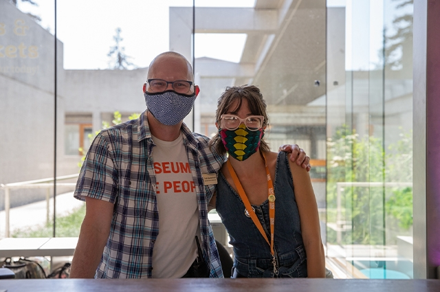 Two staff members at the ticketing booth smile for the camera, while wearing masks.