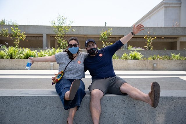 Two people wearing masks pose excitedly in the OMCA garden.