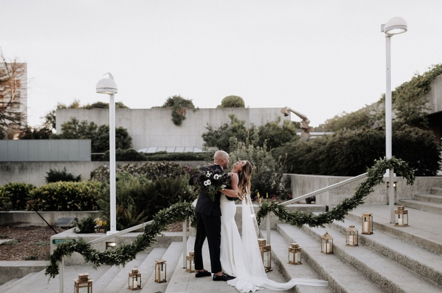 A bride and groom embrace at their wedding on the steps in the OMCA Gardens