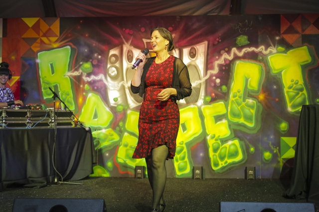 A woman speaking into a microphone on stage