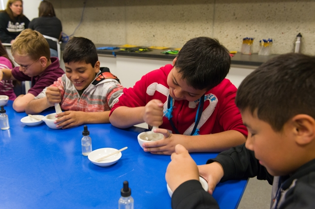 Children making paint from mortar and pestle