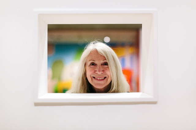 A woman looking through a square look-through of a white wall at the Oakland Museum of California