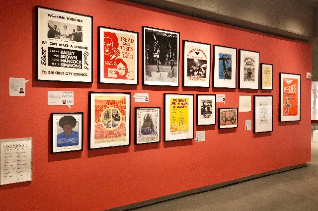 Collection of political posters from the All of Us or None Collection arranged on a wall inside OMCA's Gallery of California History