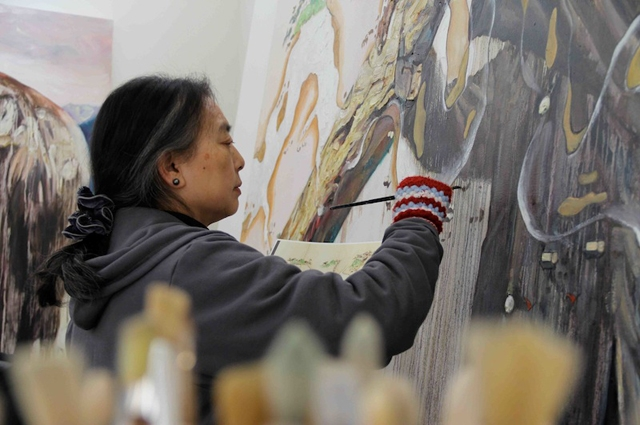 The artist Hung Liu painting in her studio