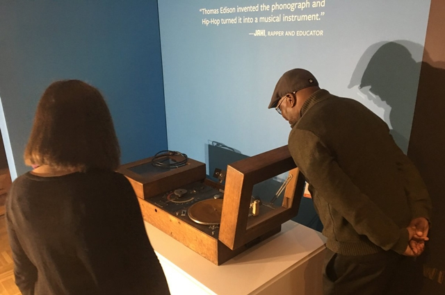 Jahi of PE 2.0 looking at a 1928 Edison turntable at the Oakland Museum of California