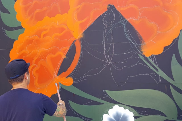Oakland artist Jet Martinez at work on a mural for the Oakland Museum of California