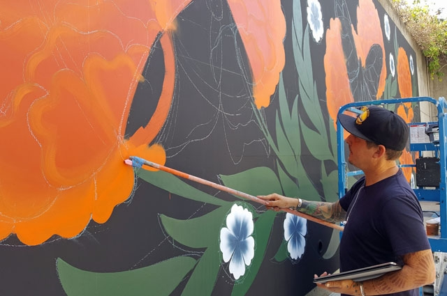 Oakland artist Jet Martinez painting a mural of Monarch Butterflies at the Oakland Museum of California
