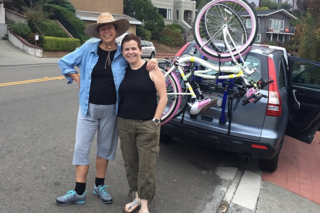 Lori and Kelly stand side by side next to their car packed for Burning Man