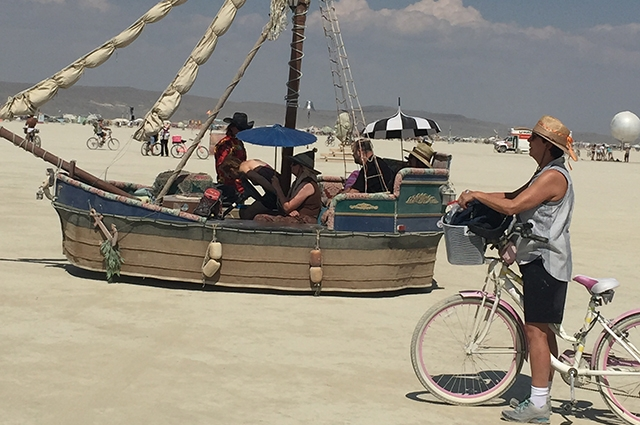 Lori stands with her bike beside a large boat in the desert at Burning Man