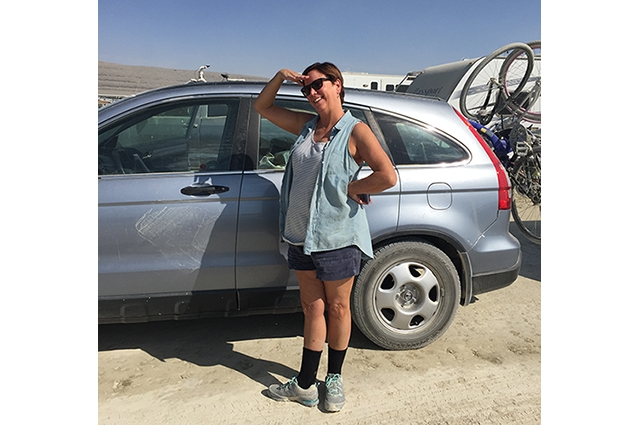 Lori smiles next to her car in Black Rock Desert