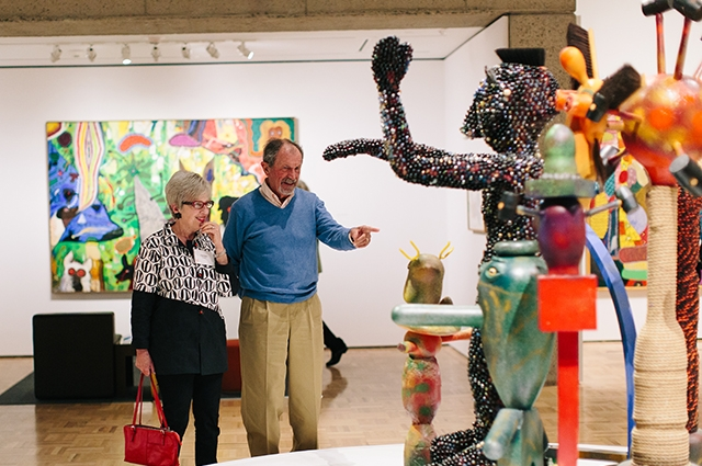 Two people smile and point at a large colorful sculpture