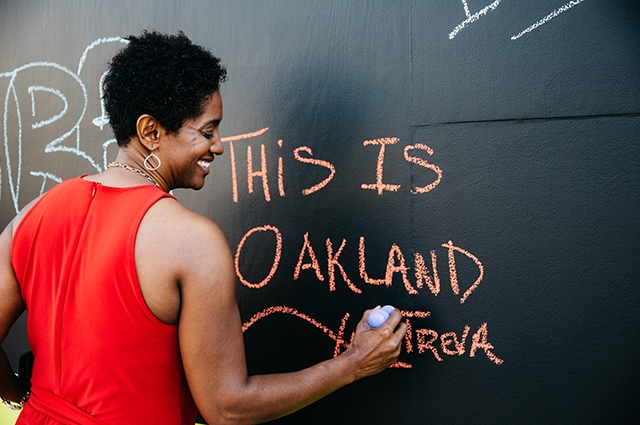 A woman writes This Is Oakland on the OCMA chalkboard wall.
