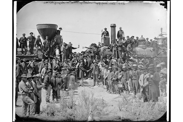 Black and white image of a large group of people standing in front of a railroad; the famous photo: East and West Shaking Hands