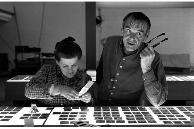 Black and white photo of Charles and Ray Eames choosing slideshow slides
