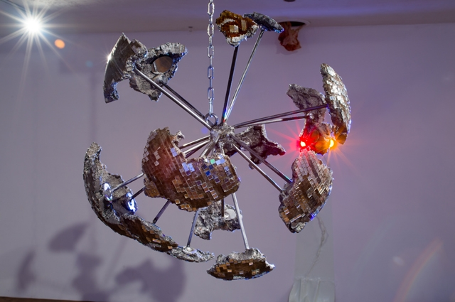A sculpture of a deconstructed disco ball with fragments hanging by silver rods