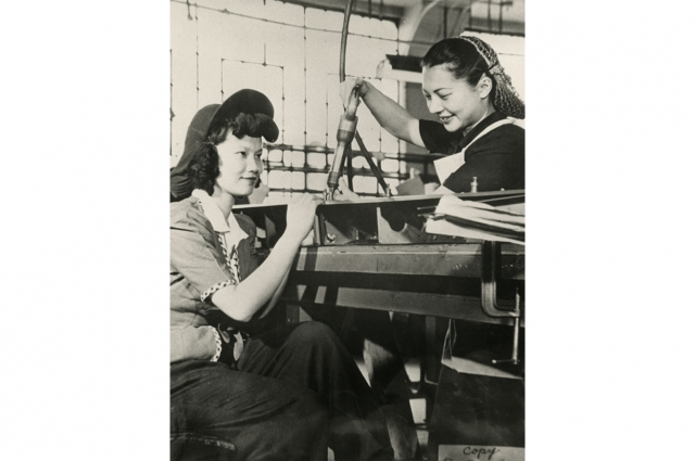 Black and white image of two women working in a factory