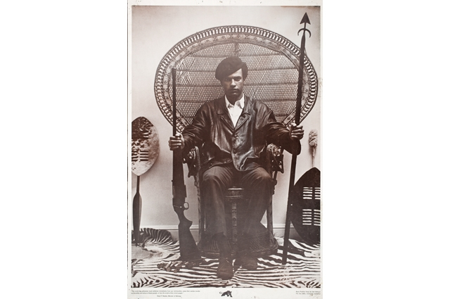 Huey Newton sits in a large wicker chair holding a gun and a spear