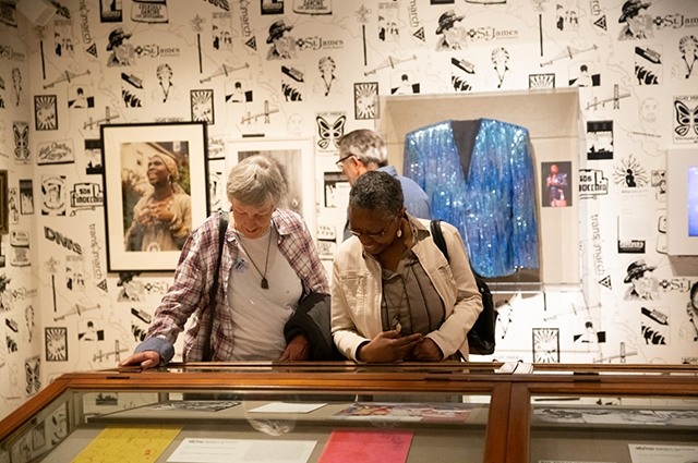 Two women smile as they look down at objects inside of a wooden case. Behind them are colorful artifacts and photos hanging on the wall