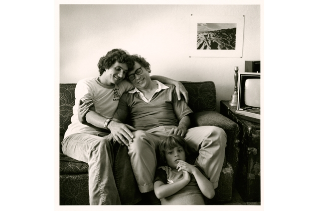 Black and white image of Tony and Alan embracing on the couch while a child, Jon, sits on the floor