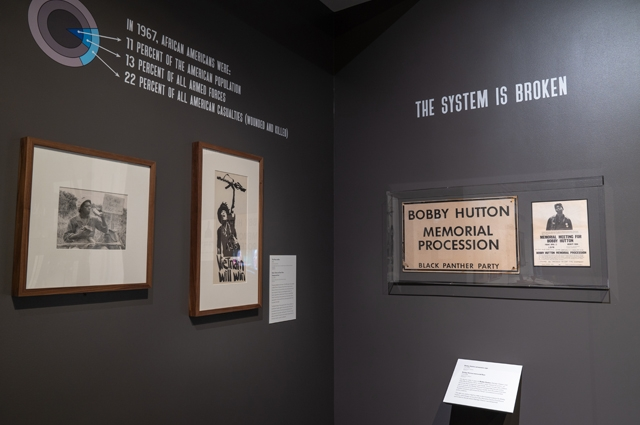 A corner of the exhibit with one wall reading: THE SYSTEM IS BROKEN and several black and white photos hanging on the walls