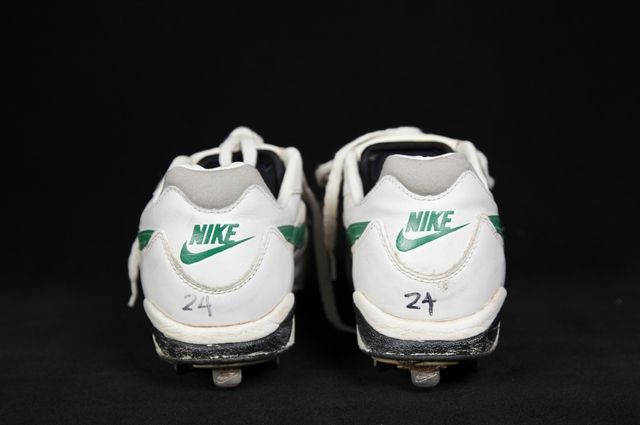 The backs of 2 White Nike cleats with green logo and the number 24 handwritten in black marker