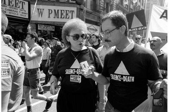 A black and white image of a man and woman at a crowded march, both with signs that read: Silence=Death