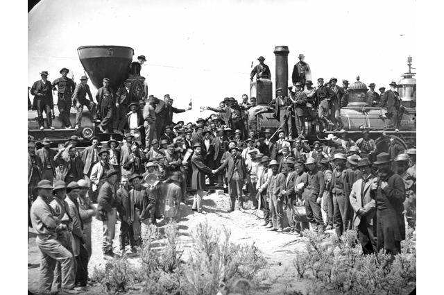 A black and white image of a large group of men standing around a train white two men in the foreground shake hands