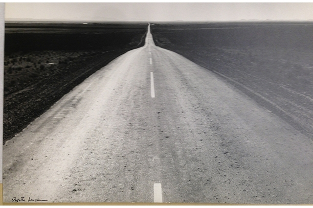 Black and white image of a long stretch of highway in the Great Plains