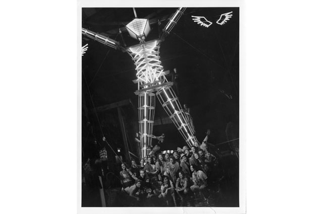 A black and white photo of a group of people gathered at the bottom of the Burning Man sculpture