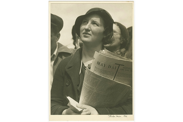 Black and white image of a woman in a crowd holding a newspaper that reads: May Day